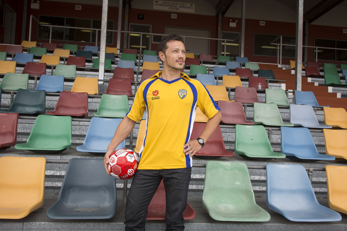 Thilo Kunkel in football jersey holding football at Griffith University sports track