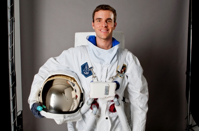Tim Gibson, Griffith business graduate, in astronaut suit with helmet under his arm.