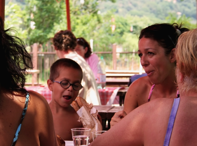 A group of three women with a child at a table in a public setting like a restaurant.