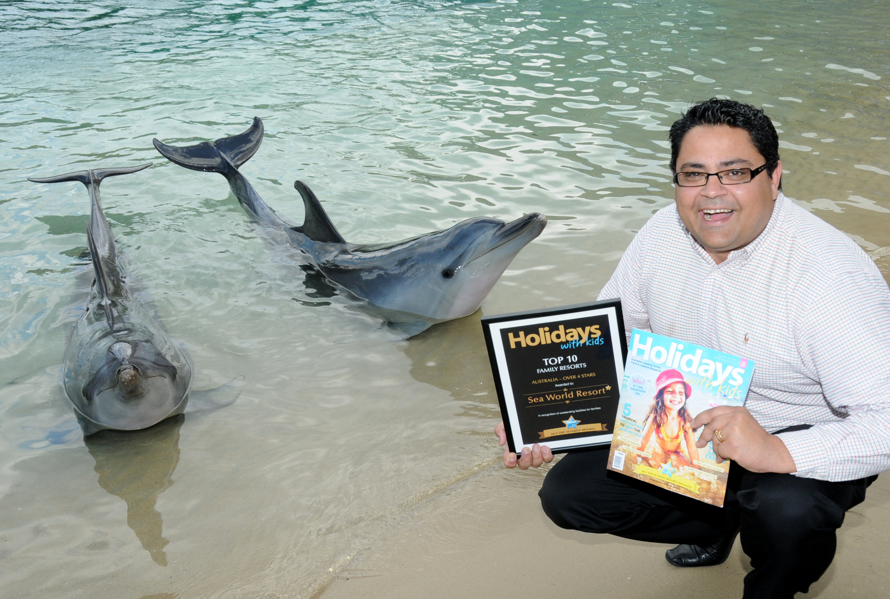 Bikash Randhawa, with dolphin friends at Sea World, has gone from business graduate to business leader since coming to the Gold Coast