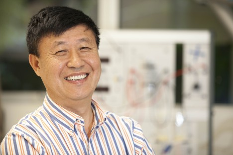 Professor Huijun Zhao, Director of the Centre for Clean Environment and Energy, smiling in front of lab equipment