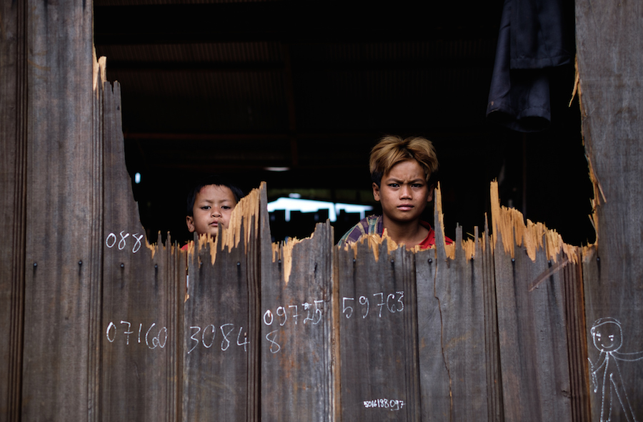 Two children stare through a hole in their house caused by Atork during his rampage through a village in Romnea commune, Mondulkiri