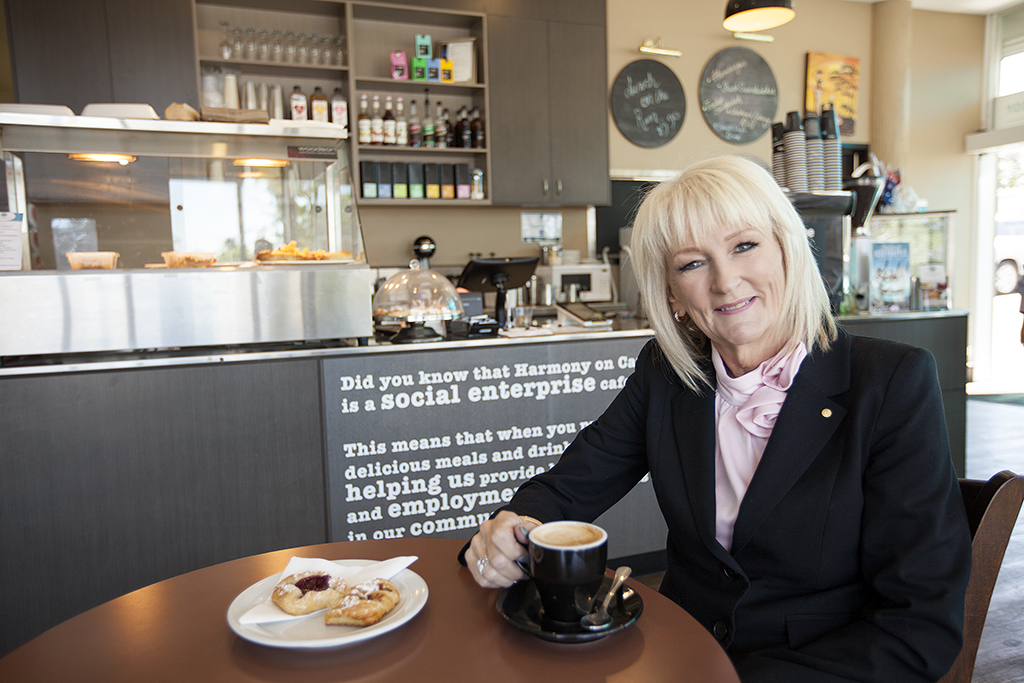 Gail Ker OAM, sitting in a coffee shop, is a force for positive impact and change in the Logan migrant community